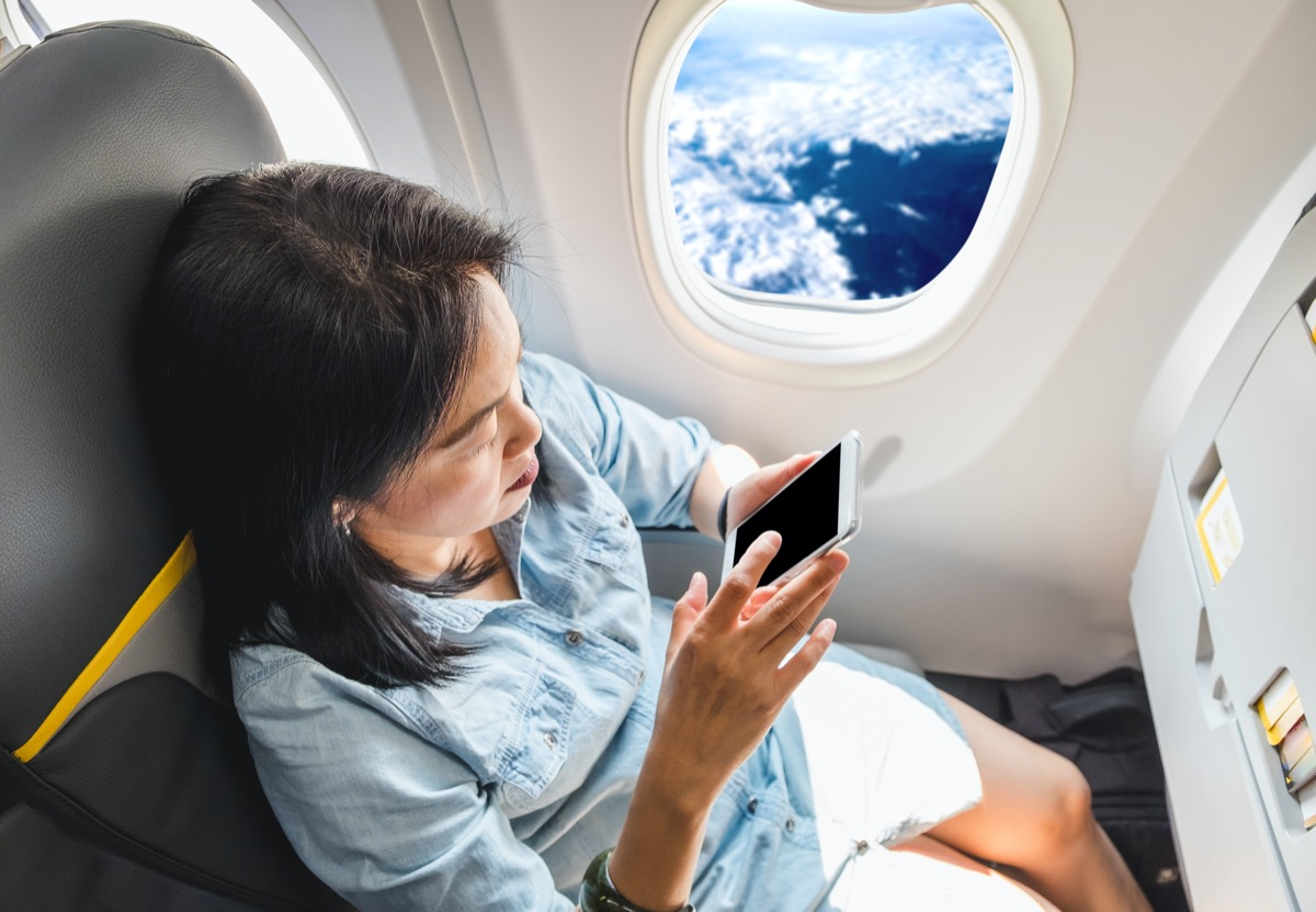 asian woman using her phone on the plane