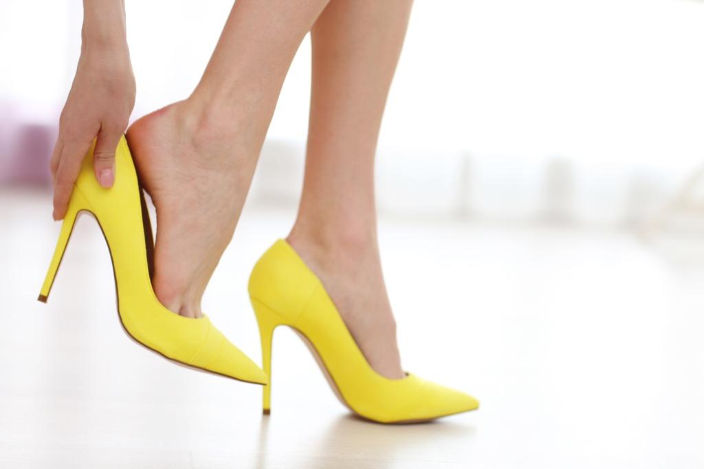 woman slipping on yellow shoes