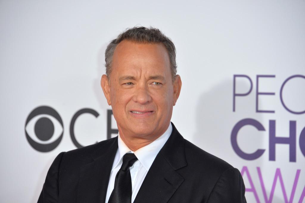 Tom Hanks in suit, half-smiling, celebrity grandparent