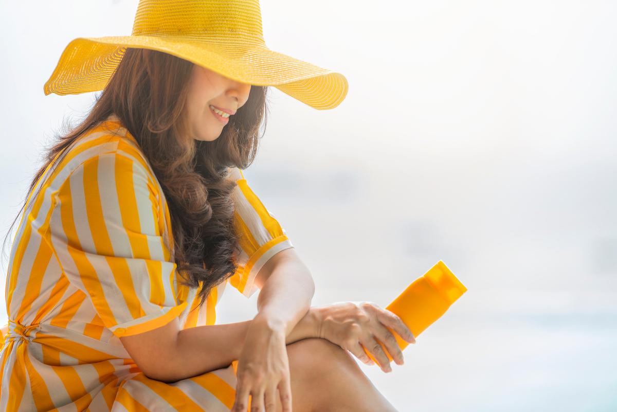 profile of asian woman wearing yellow hat applying sunscreen