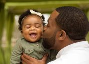 young black dad kissing baby daughter