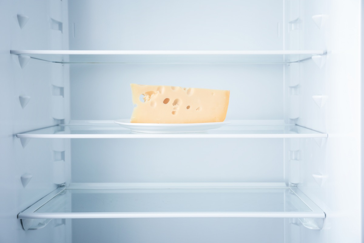 a block of cheese in an empty refrigerator