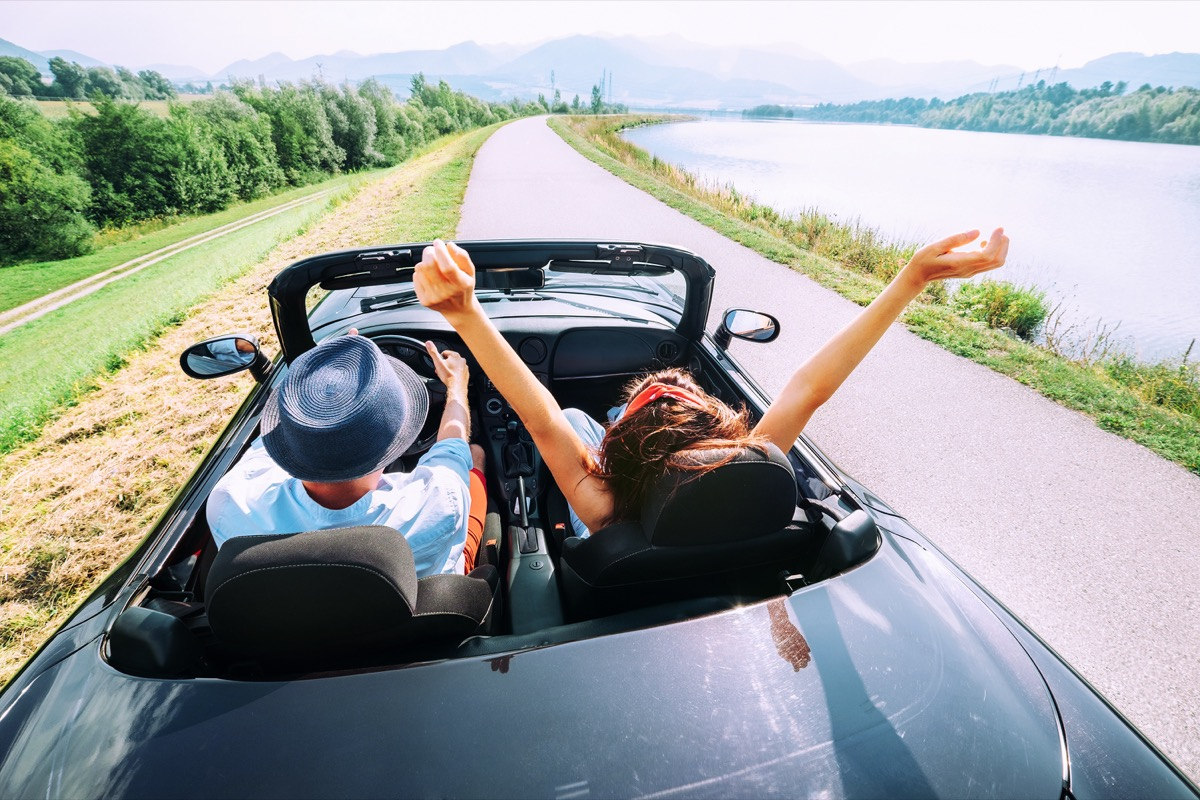 Couple driving a convertible down the road adjacent to the water for a weekend getaway