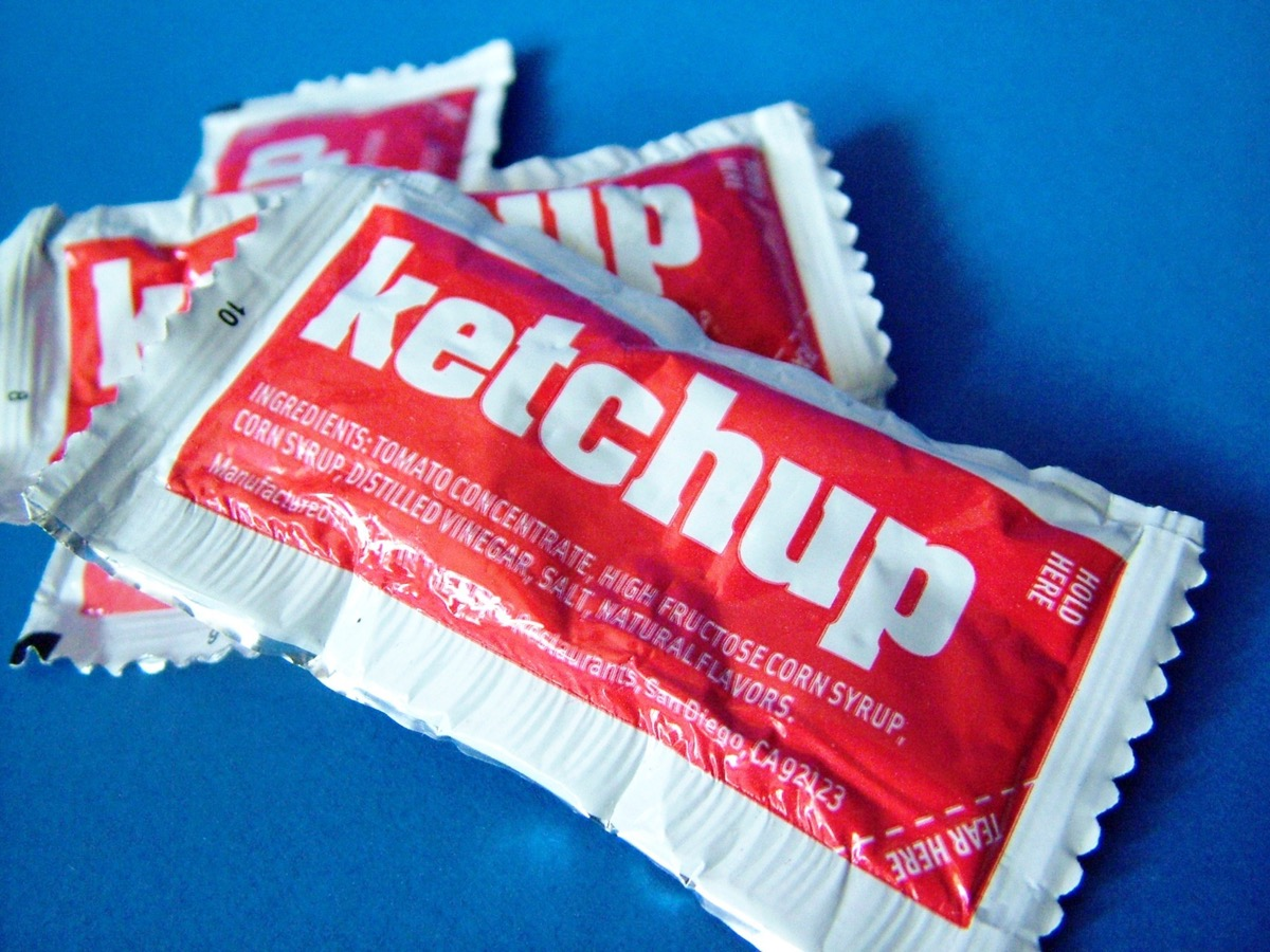 ketchup packets against a blue background
