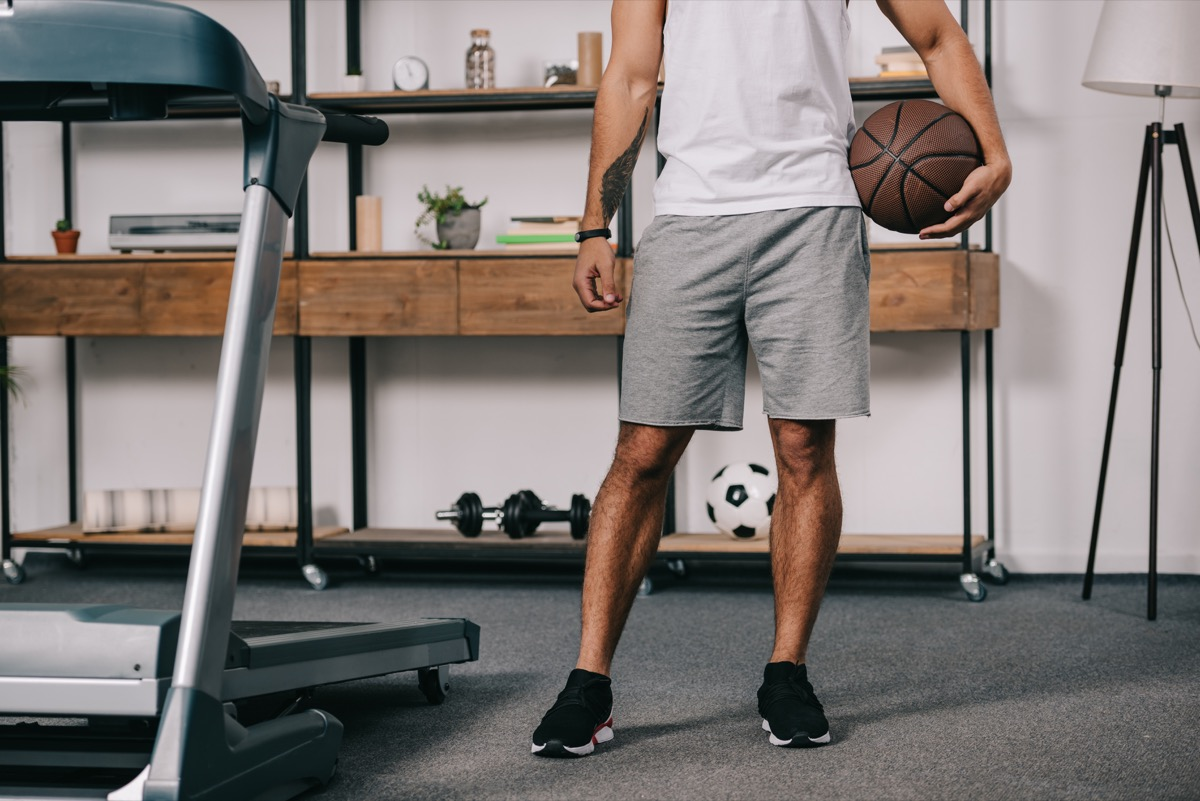 man holding a basketball standing next to a treadmill