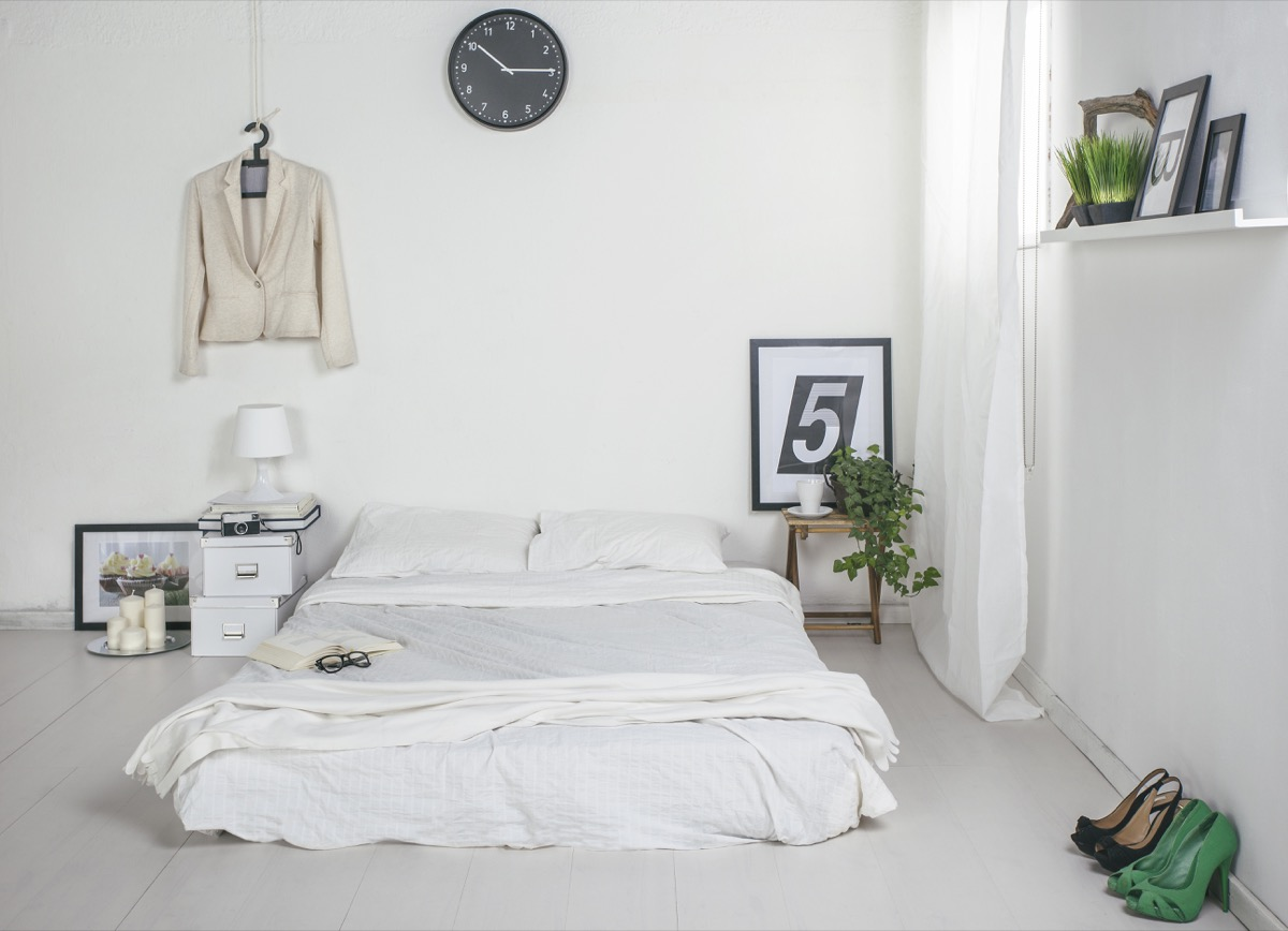 a modern white bedroom with the mattress placed directly on the floor