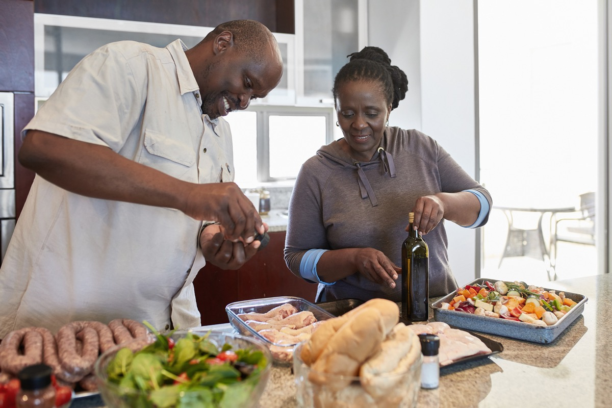 Senior couple preparing food at kitchen counter. Female is looking at male seasoning meat. They are at home. (Senior couple preparing food at kitchen counter. Female is looking at male seasoning meat. They are at home.