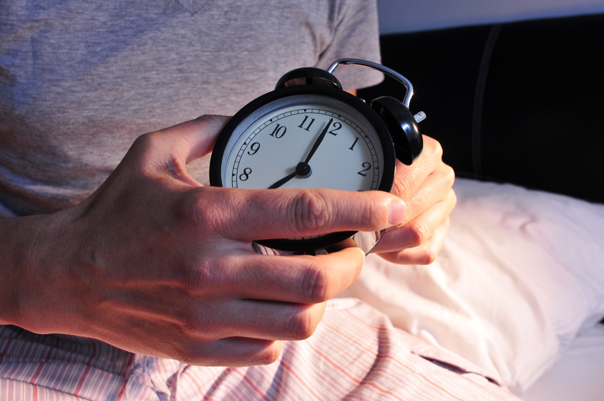 Person setting clock at bed time for alarm clock