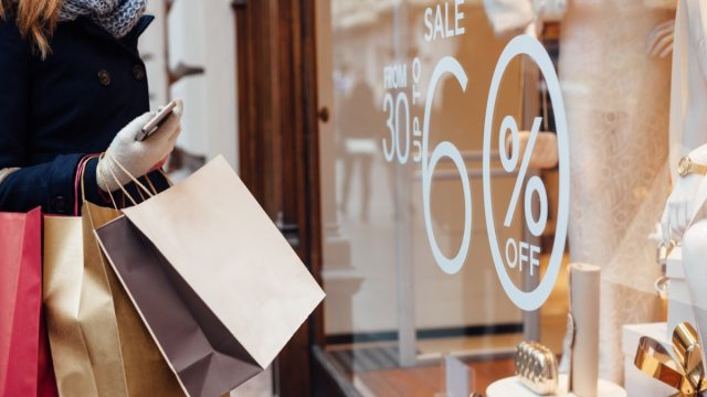 Woman shopping and looking at a window marked with a sale