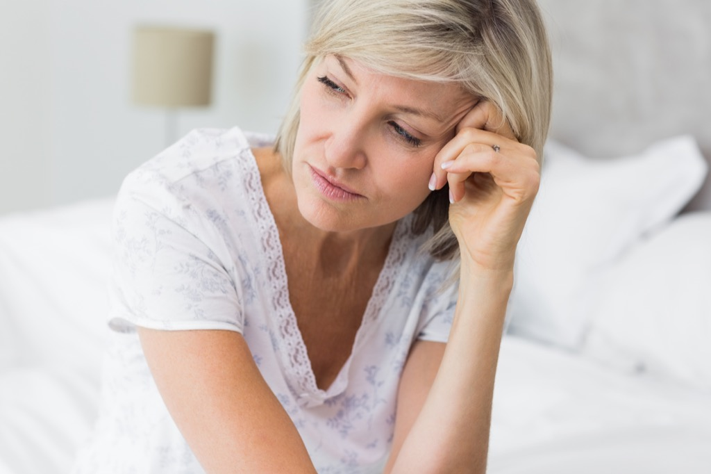 upset woman on bed, midlife crisis signs