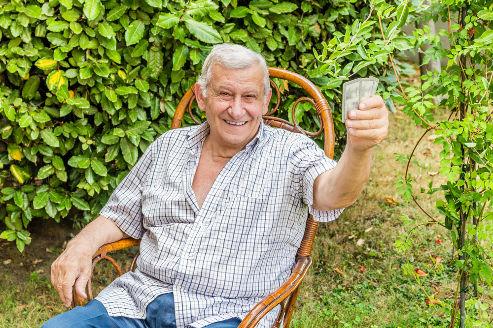 old happy man holds up playing cards.