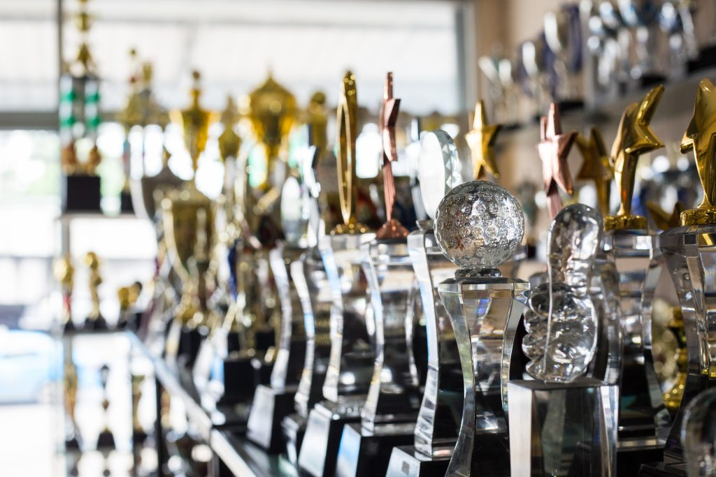 sports trophies in trophy case over 40 home - cat puns