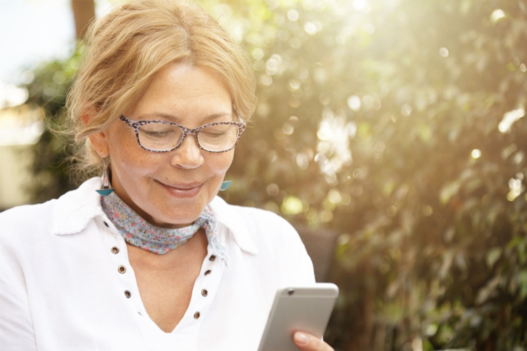 older woman looking at her phone - how to dress over 50