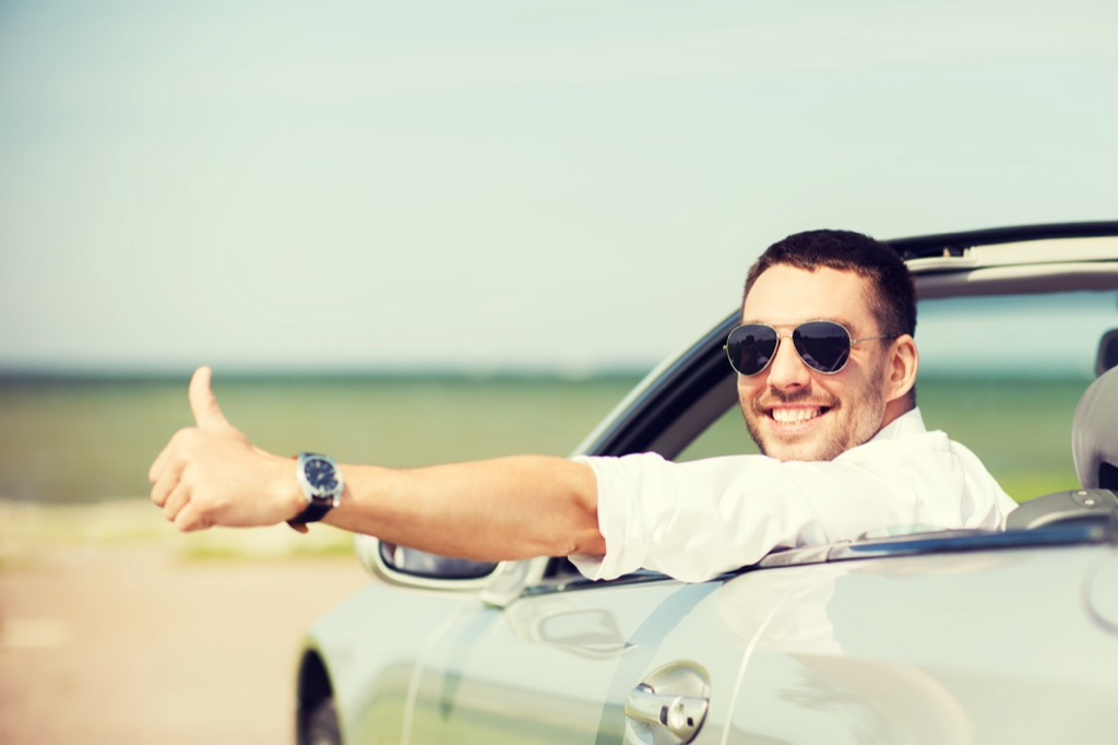 man with a thumbs up in a convertible