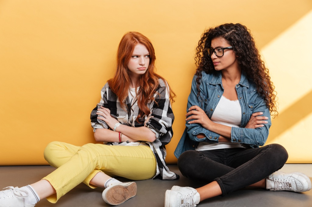 white woman with red hair and black woman with curly hair and glasses look at each other angrily