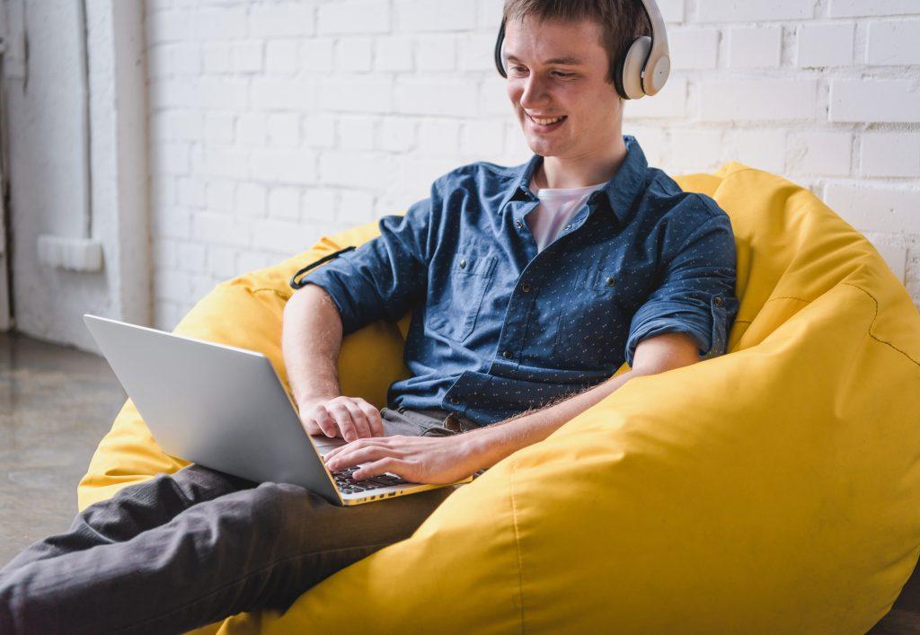 man laptop headphones beanbag chair