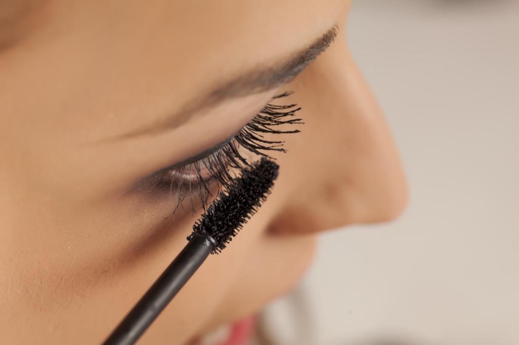 woman applying mascara, make yourself more attractive