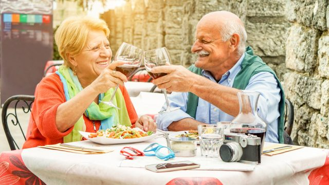 elderly couple drinks wine and eats in Italy