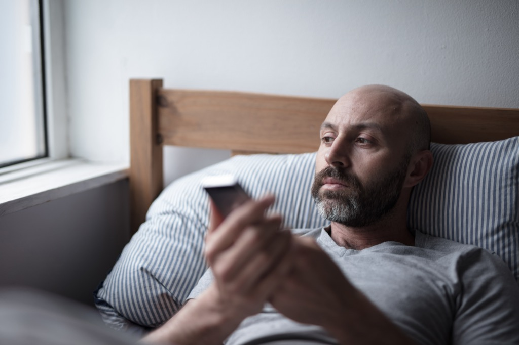 man looking sad in bed, worst things about an empty nest