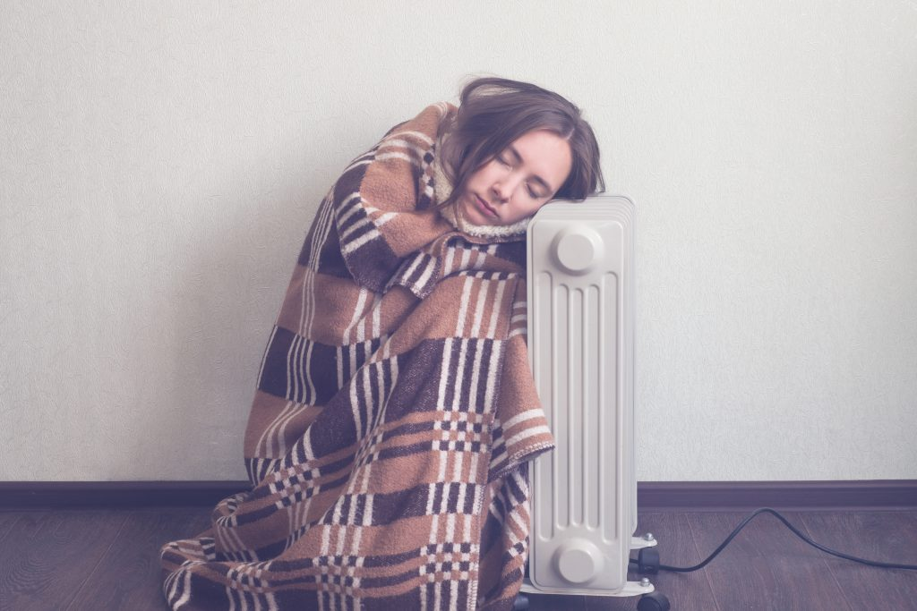 woman by heater staying warm