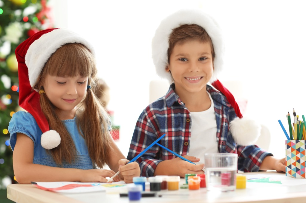 Little boy and girl wearing Santa hats and doing crafts