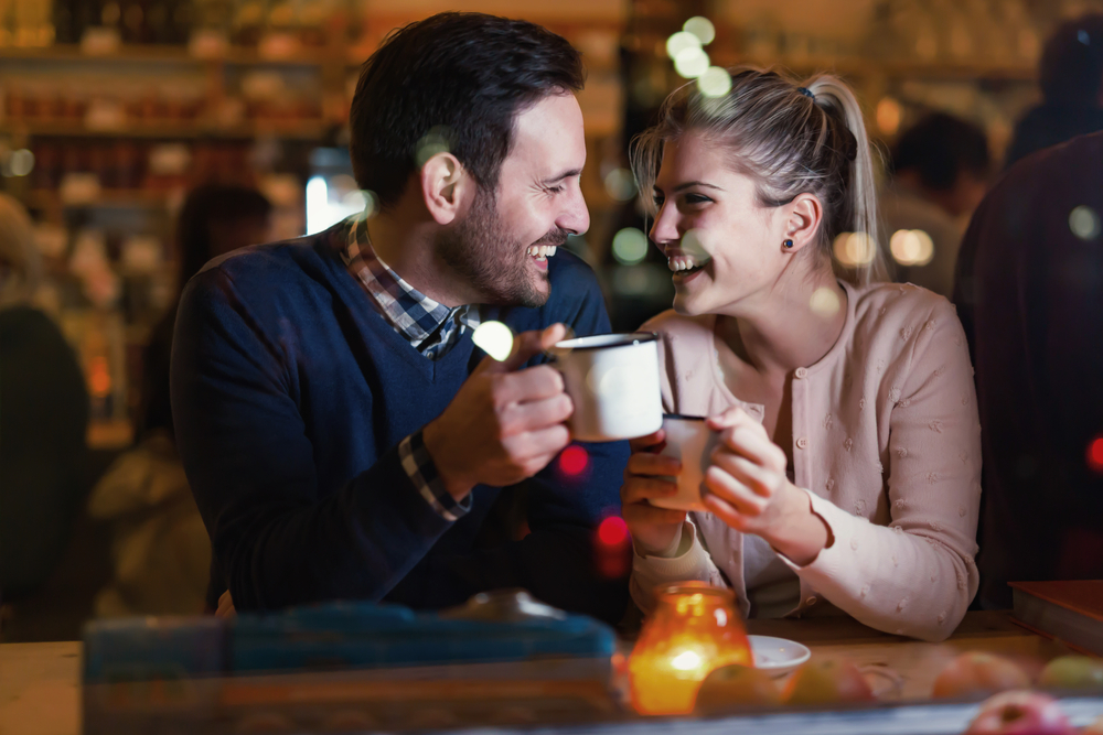 man and women on date with drinks and candle - what to say on a first date