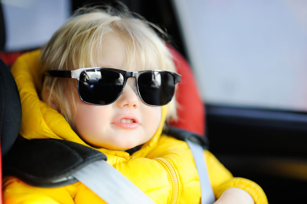 baby sitting in car, looking chill.