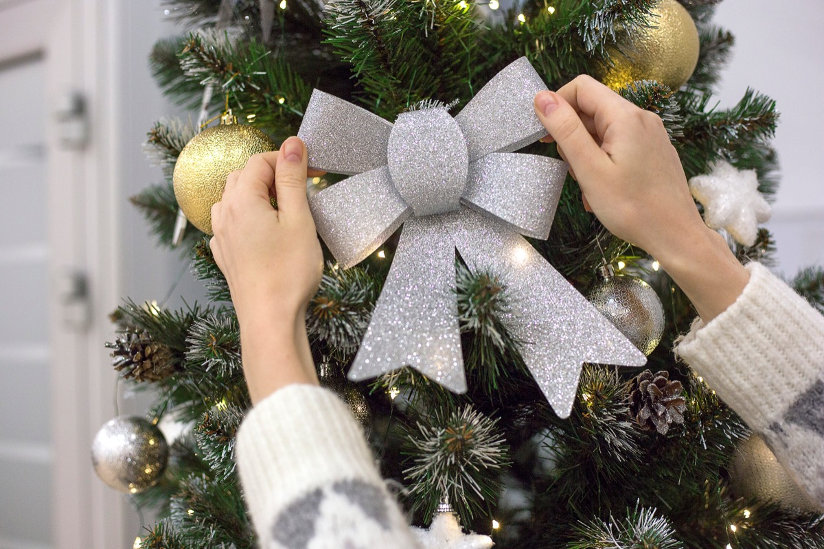 Silver Christmas bow by a Christmas tree