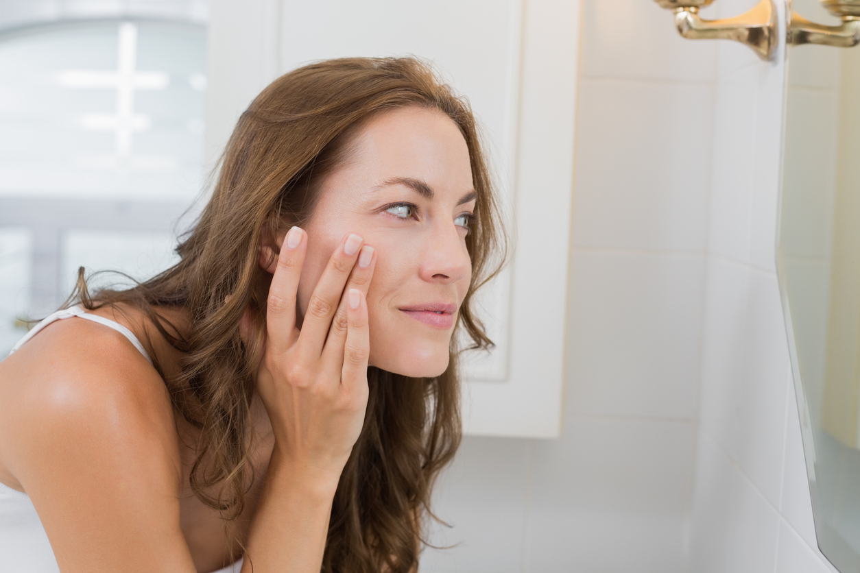 Side view of a woman examining her face in the mirror in the bathroom at home