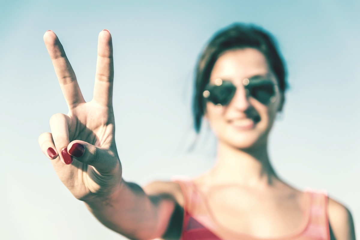 young woman giving peace sign