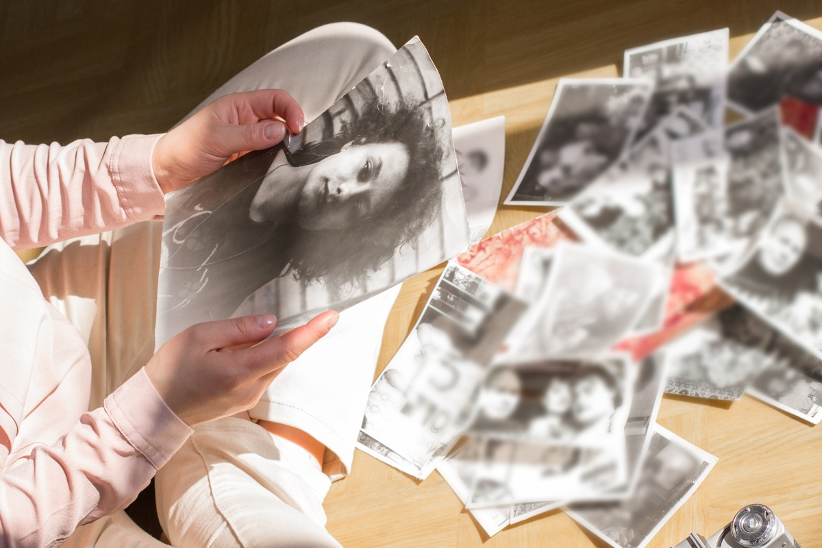 young woman sitting on the floor looking at pictures