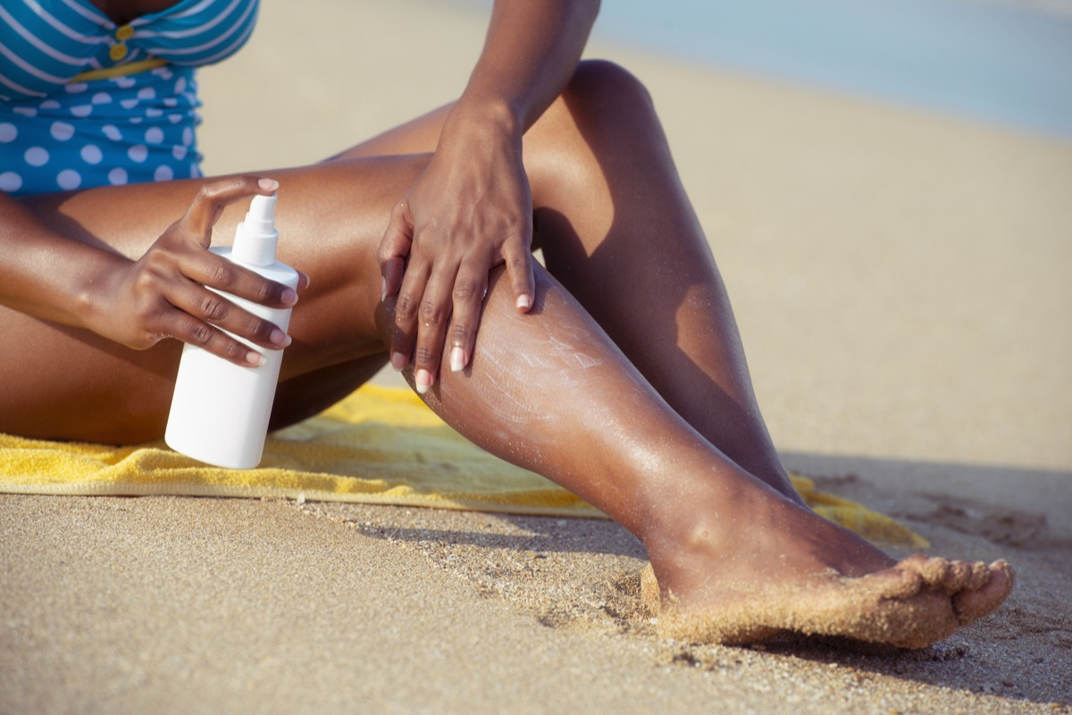 Black woman applying, spraying sun protection cream on her legs, habits after 40