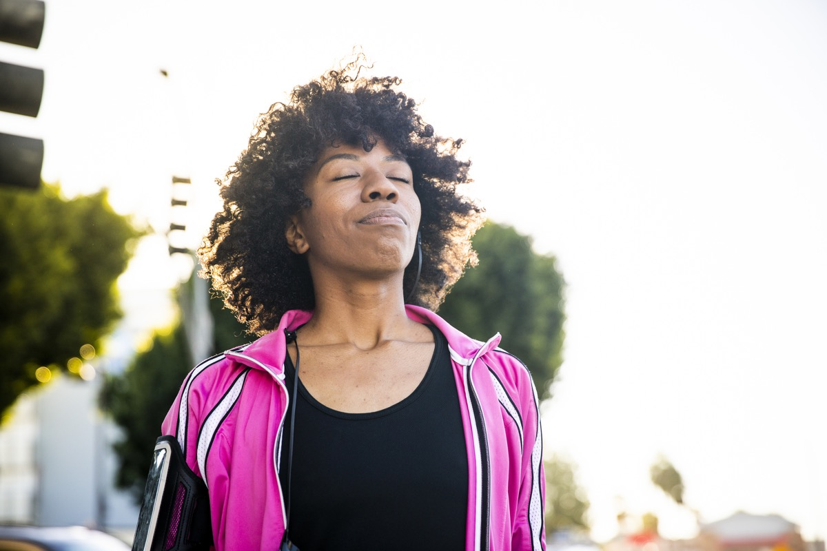 Black woman takes deep breath outdoors, habits after 40