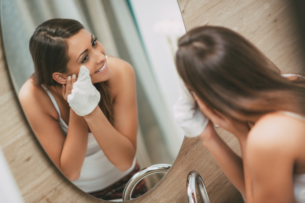 Woman using makeup wipe Anti-Aging Tips You Should Forget