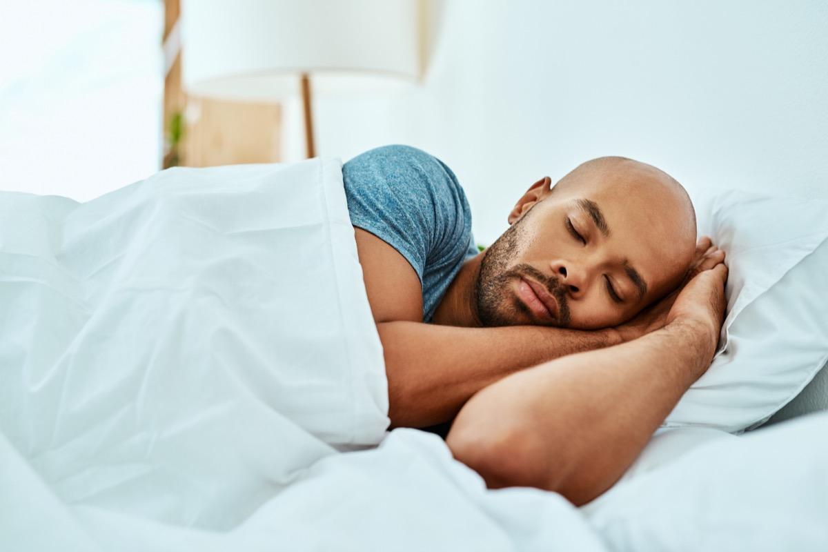 Black man sleeping in his bed
