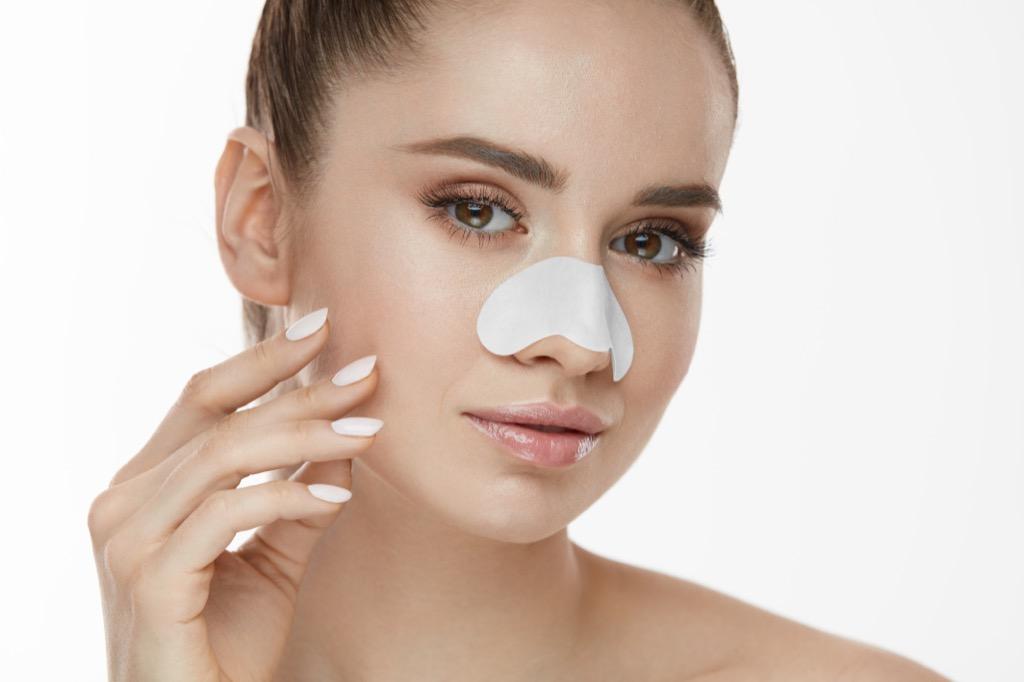 Woman using pore strip Body Flaws