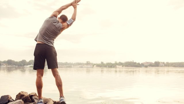 Runner stretching to boost his metabolism, exercise