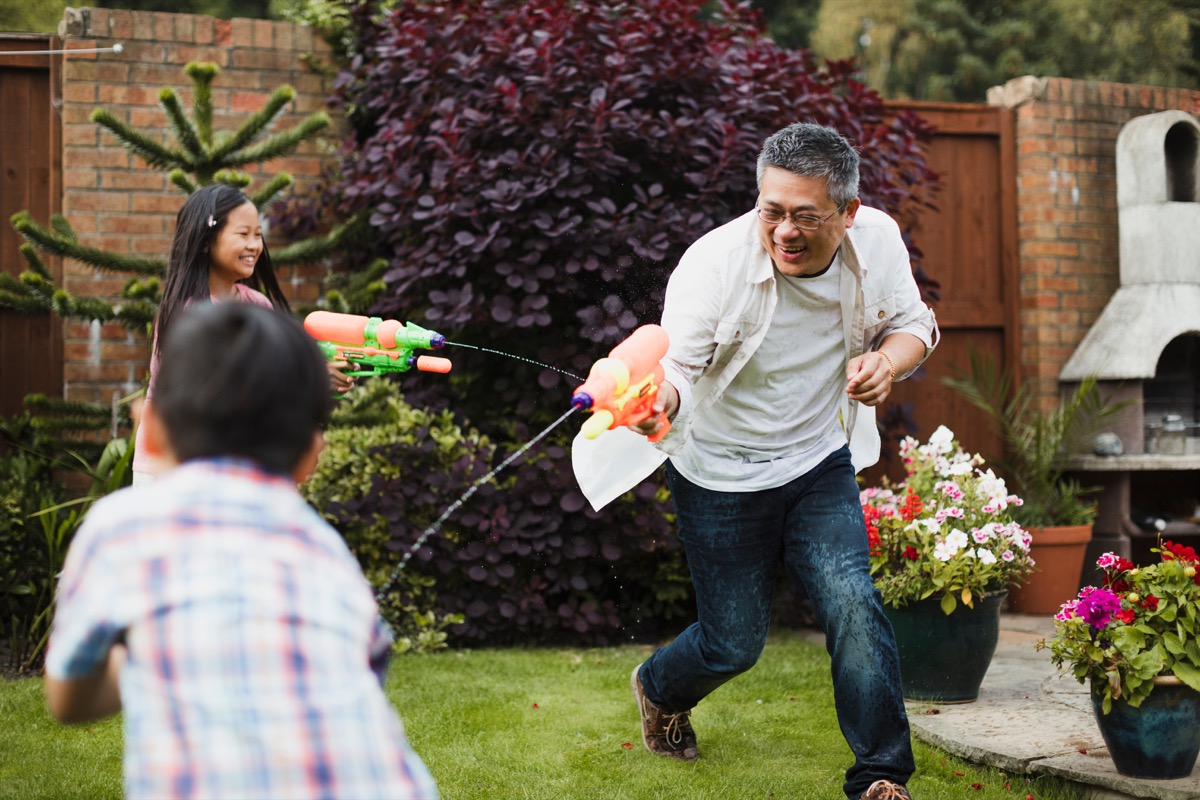 Asian family having a water fight
