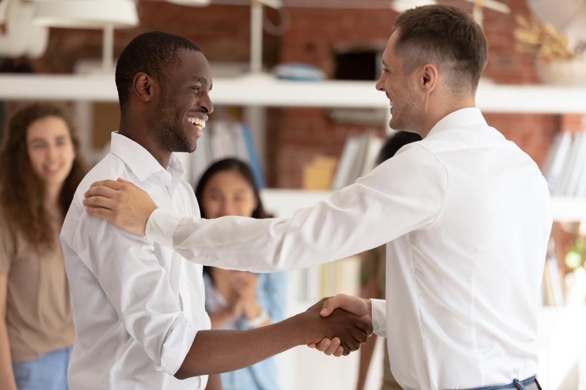 Boss thanking congratulating employee shaking hands multicultural