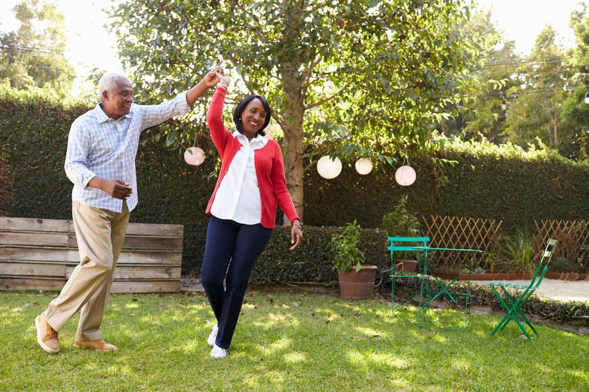 Older black couple dancing in backyard