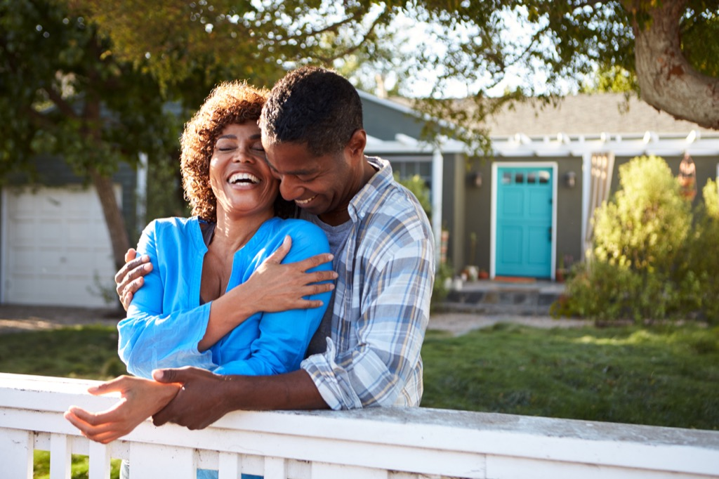 couple outdoors by house laughing crazy health benefits of laughter