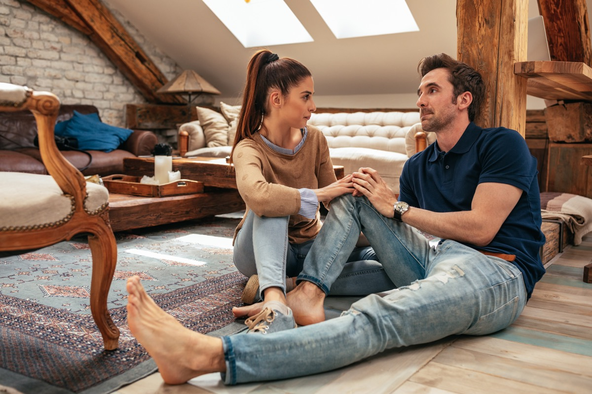 Couple talking sitting on floor man being vulnerable woman being supportive