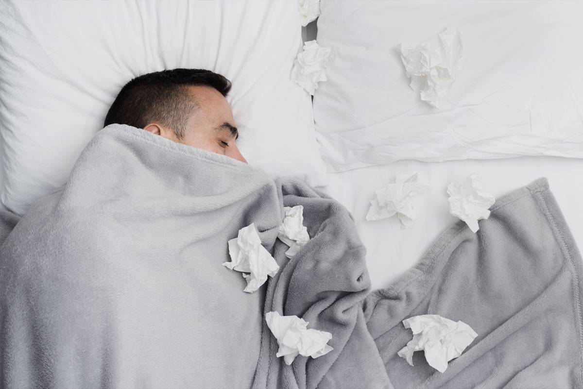 sick white man in bed with tissues