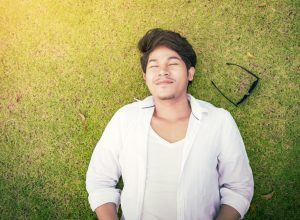 young asian man lying on the grass with his eyes closed and his sunglasses next to him