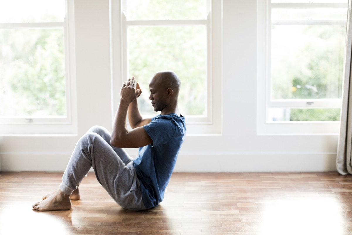 black man doing sit ups on a hardwood floor at home