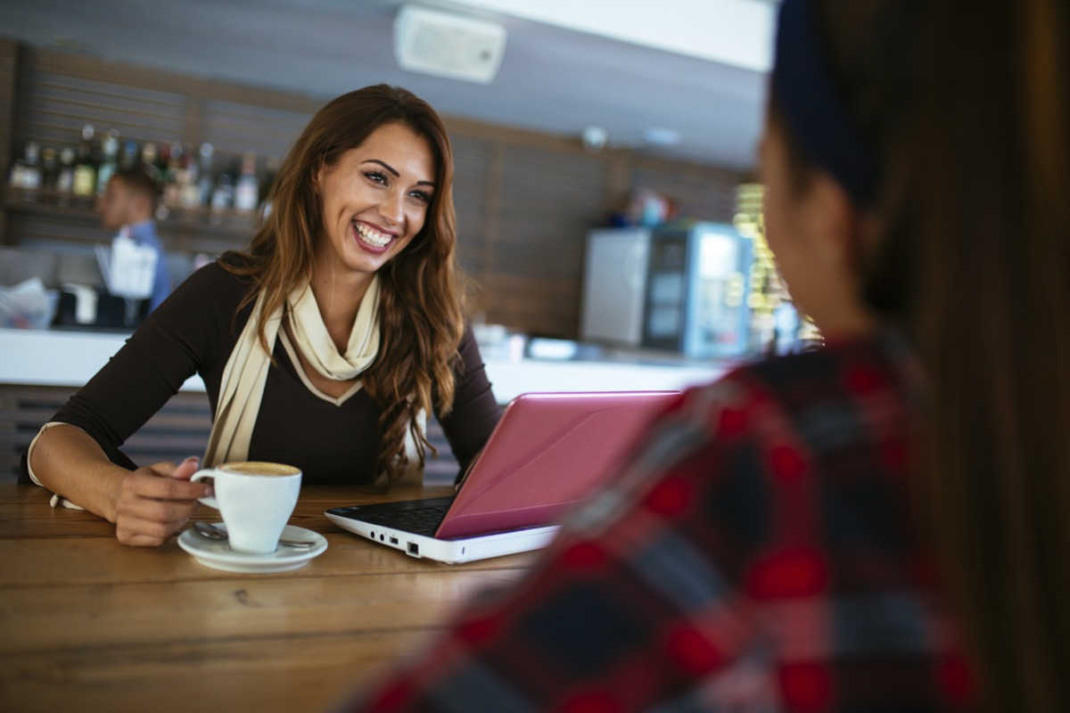young woman smiling with her computer and coffee talking to another woman at a coffee shop