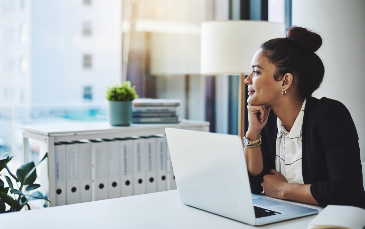latina woman at laptop in office looking out the window