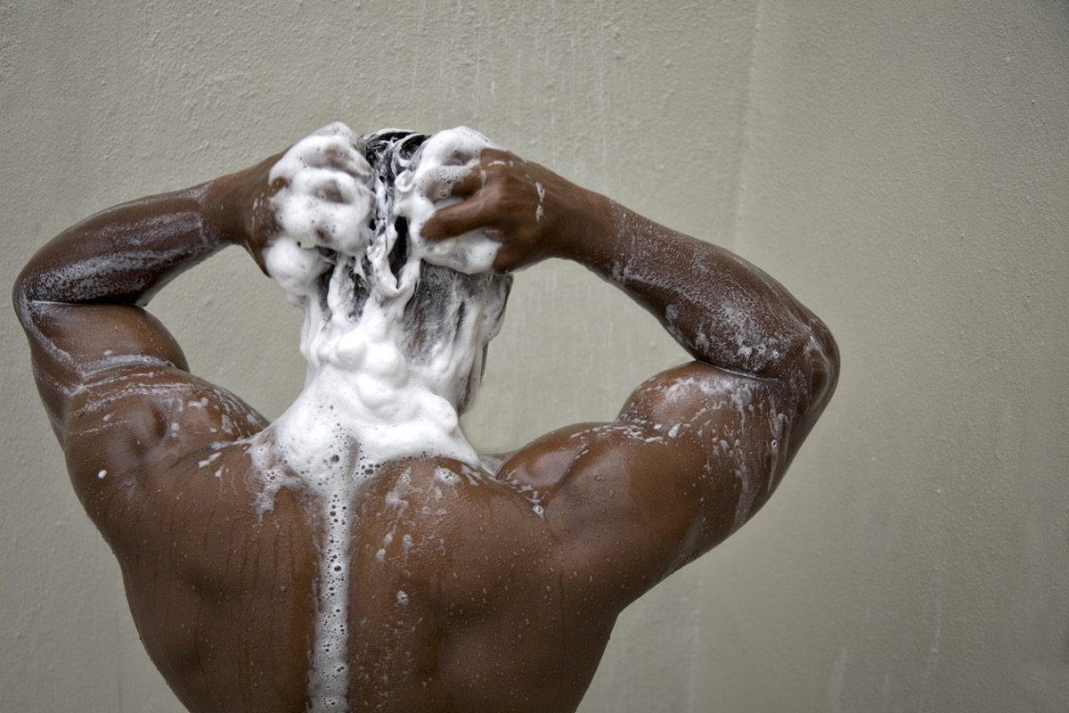 black man with his back to camera shampooing his hair in the shower