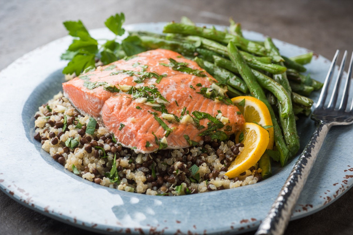 close up plate of salmon over rice and lentils with green beans