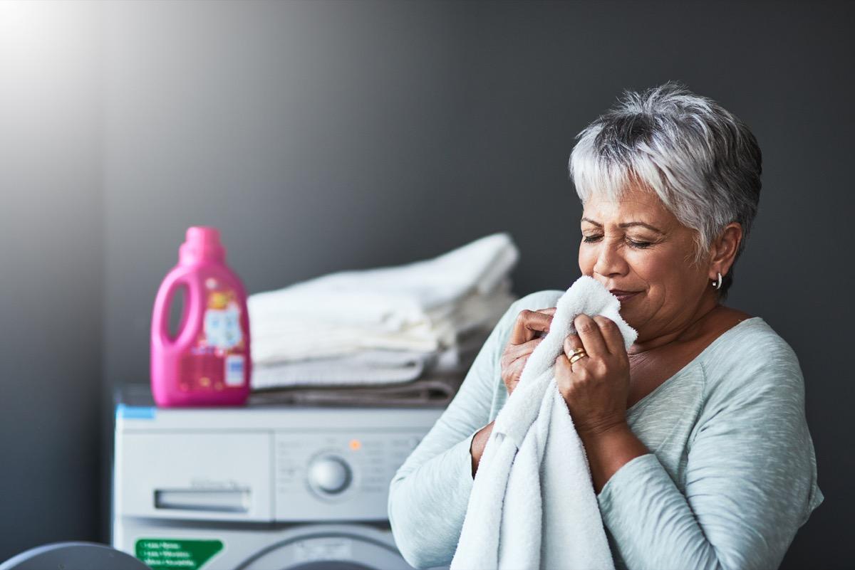 older latina woman smelling a fresh towel near the washing machine